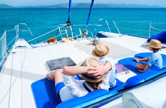 Vater mit zwei Kindern und Sonnenhut sitzen entspannt auf einem Boot im blauen Meer