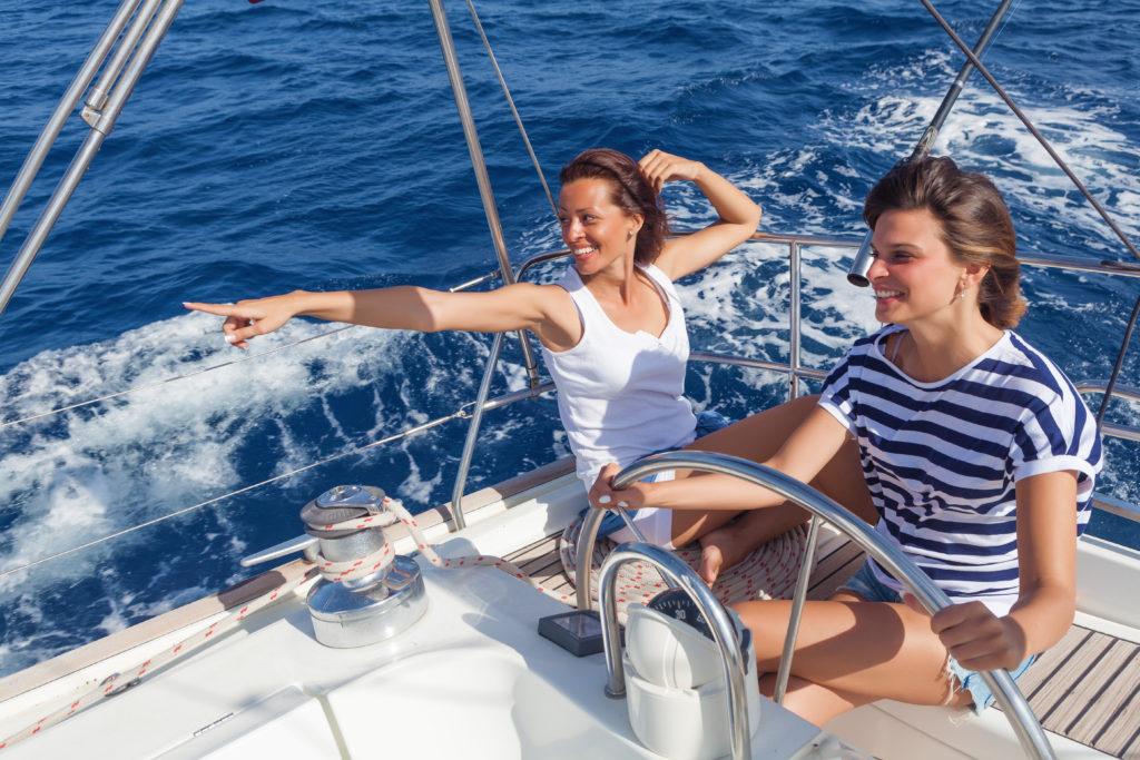 Zwei Frauen fahren mit einem Boot auf dem Wasser, eine von ihnen steuert das Boot