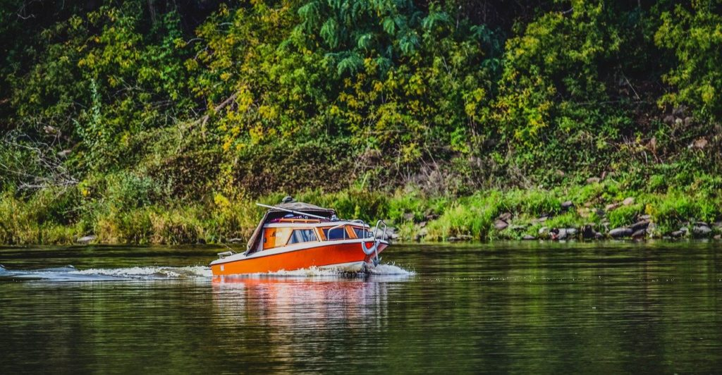 Motorboot auf dem Wasser mit grünem Hintergrund