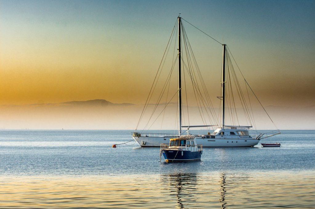 Zwei Boote bei Sonnenaufgang auf dem Meer