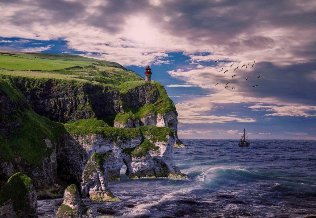 Boot neben einer Küste mit Leuchtturm auf offenem Meer