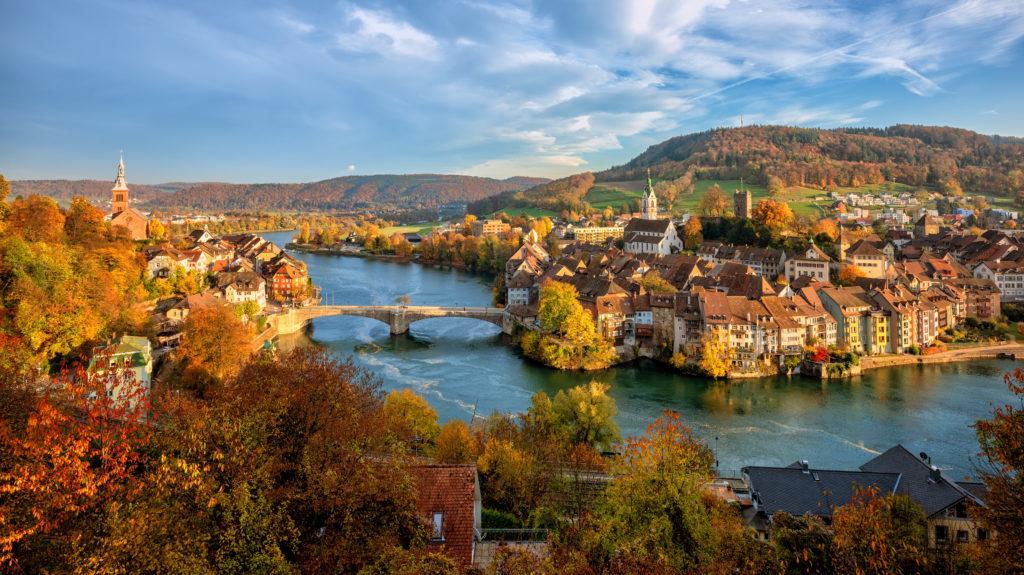 Laufenburg mit Altstadt am Rhein umringt von herbstlichen Wäldern