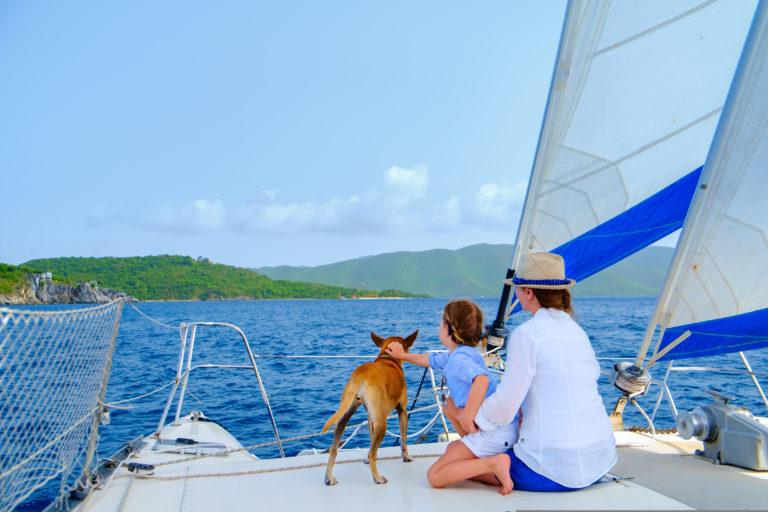 Mutter mit Tochter und Hund auf einem Segelboot auf dem Wasser