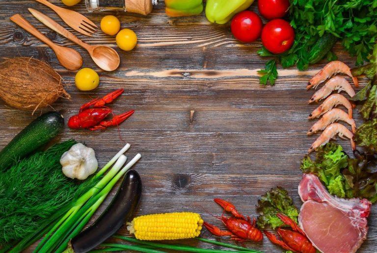 verschiedene Lebensmittel liegen auf einem Holztisch in einem Kreis angeordnet