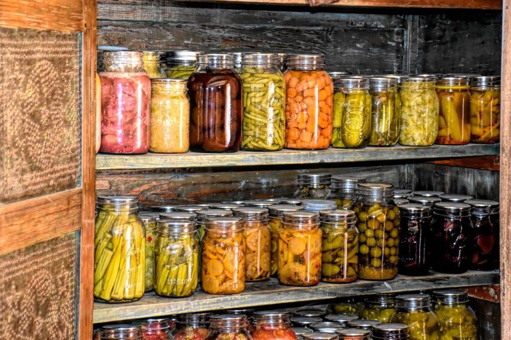 Viele verschiedene Gläser mit eingelegtem Obst und Gemüse stehen in einem Regel