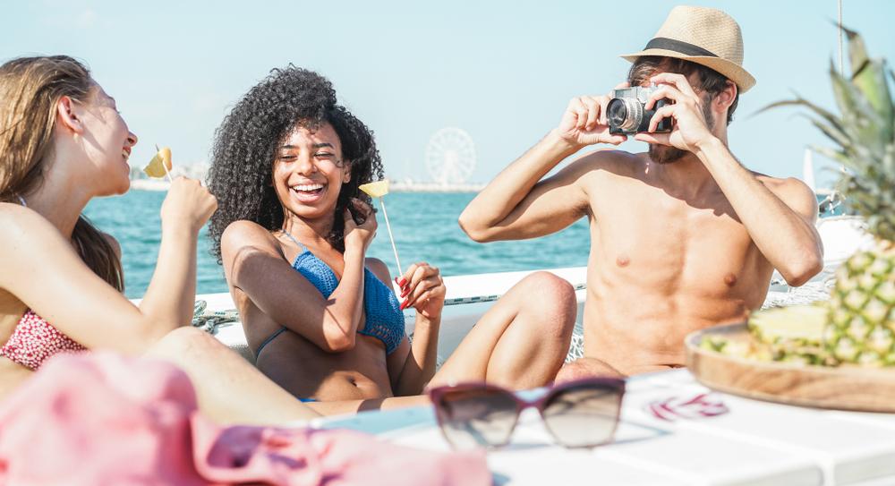 Fröhliche Freunde, die Spaß beim Fotografieren auf Bootsfeiern haben - Junge Menschen, die Ananas essen und lachen