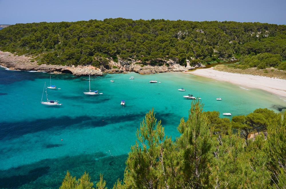 Wunderschöner Strand Cala Trebaluger mit Yachten und Booten in türkisblauem Wasser, Menorca, Balearen, Spanien