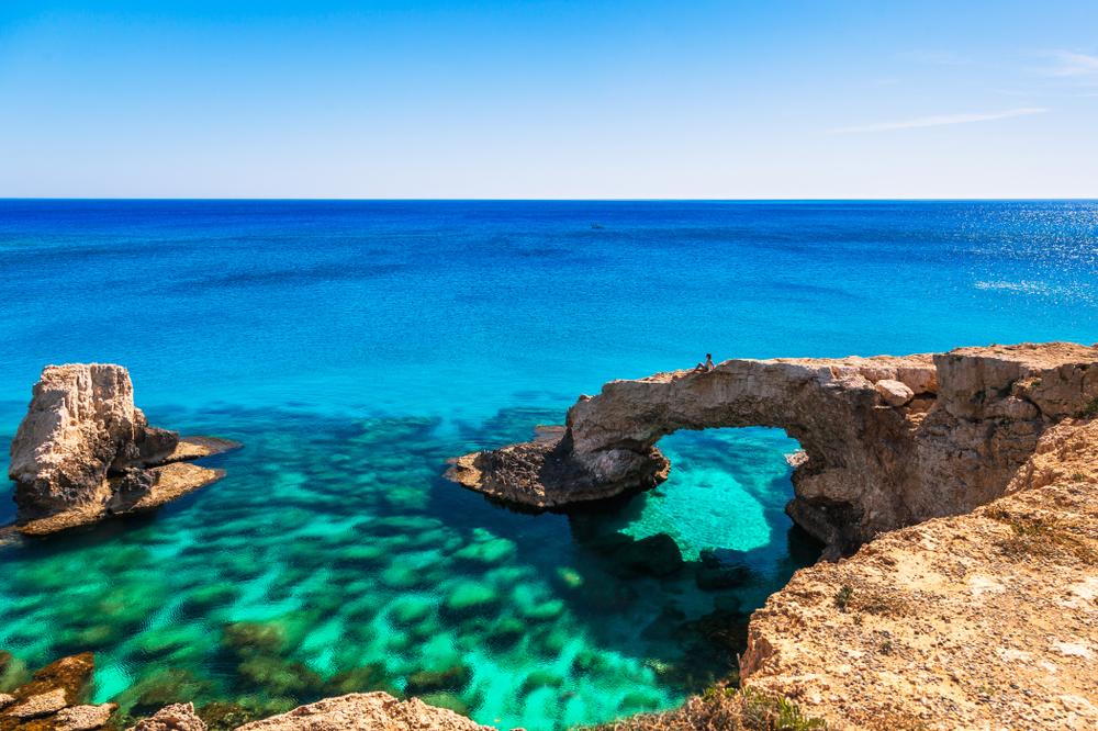 Frau auf dem wunderschönen natürlichen Felsbogen in der Nähe von Ayia Napa, Cavo Greco und Protaras auf Zypern Insel, Mittelmeer. Erstaunlich blaues, grünes Meer und sonniger Tag.