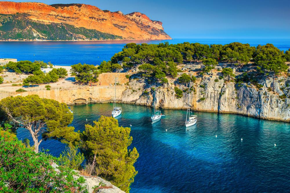 atemberaubender Aussichtspunkt auf den Klippen, Calanques de Port Pin Bucht mit Yachten und Segelbooten, Calanques National Park bei Cassis, Provence, Südfrankreich