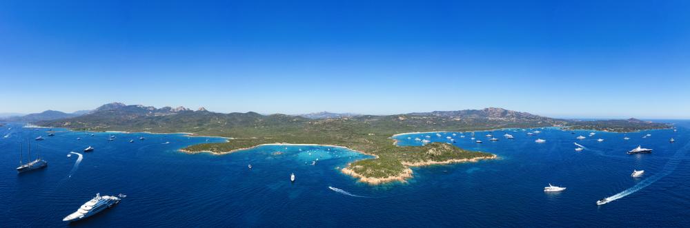 Atemberaubender Panoramablick auf einige Strände der Smaragdküste (Costa Smeralda) mit Booten und Luxusyachten, die auf einem wunderschönen türkisfarbenen, klaren Meer segeln. Liscia Ruja Strand und Petra Ruja Strand, Sardinien.