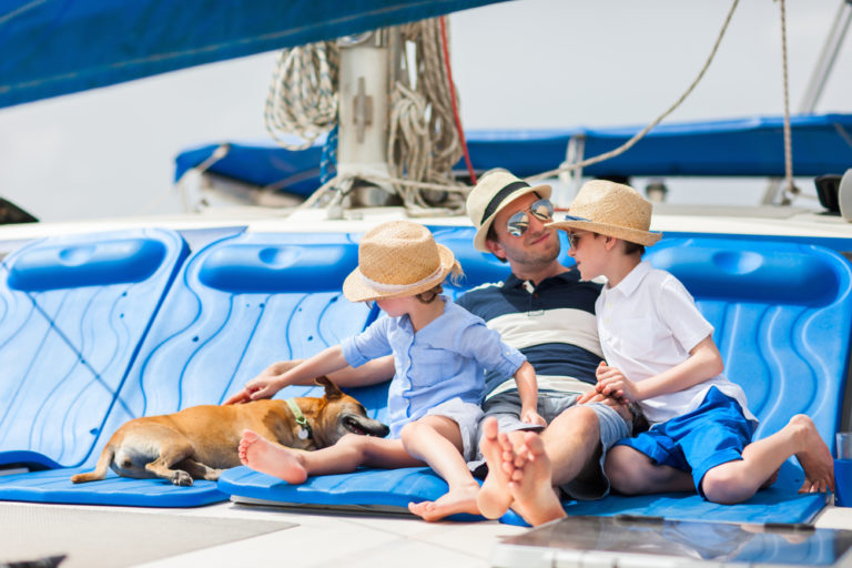 Vater sitzt mit seinen Kindern und Hund auf einem Boot