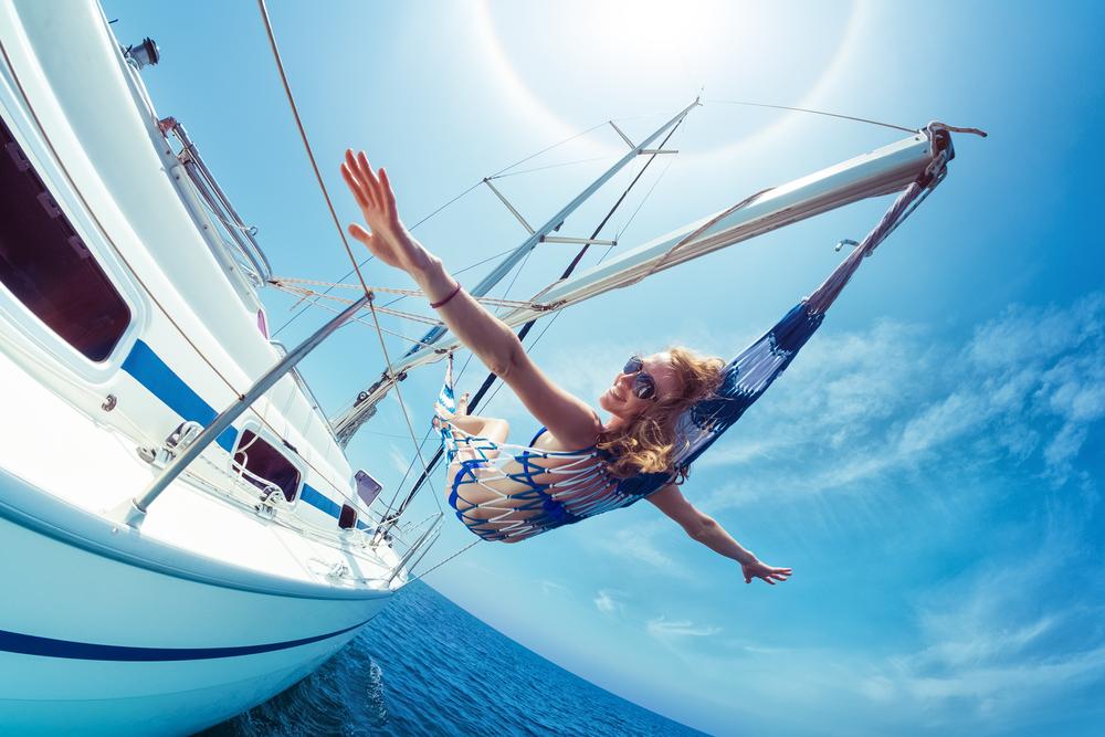 Junge Frau entspannt in einer Hängematte auf einem Boot über dem Wasser