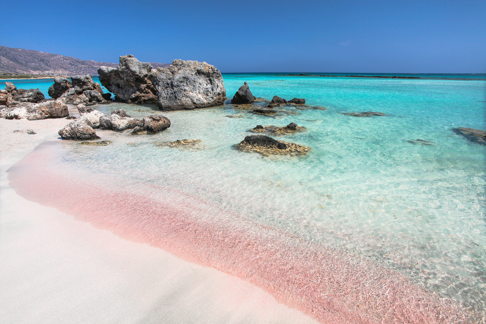 Die Welle des Meeres auf dem rosafarbenen Sand und schönen Strand mit Klippen. Küste von Kreta Insel in Griechenland. Rosa Sandstrand von Elafonisi