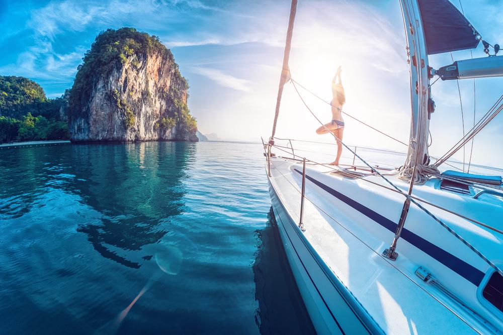 Junge Frau die auf einer Yacht steht und bei Sonnenaufgang Yogaübungen macht