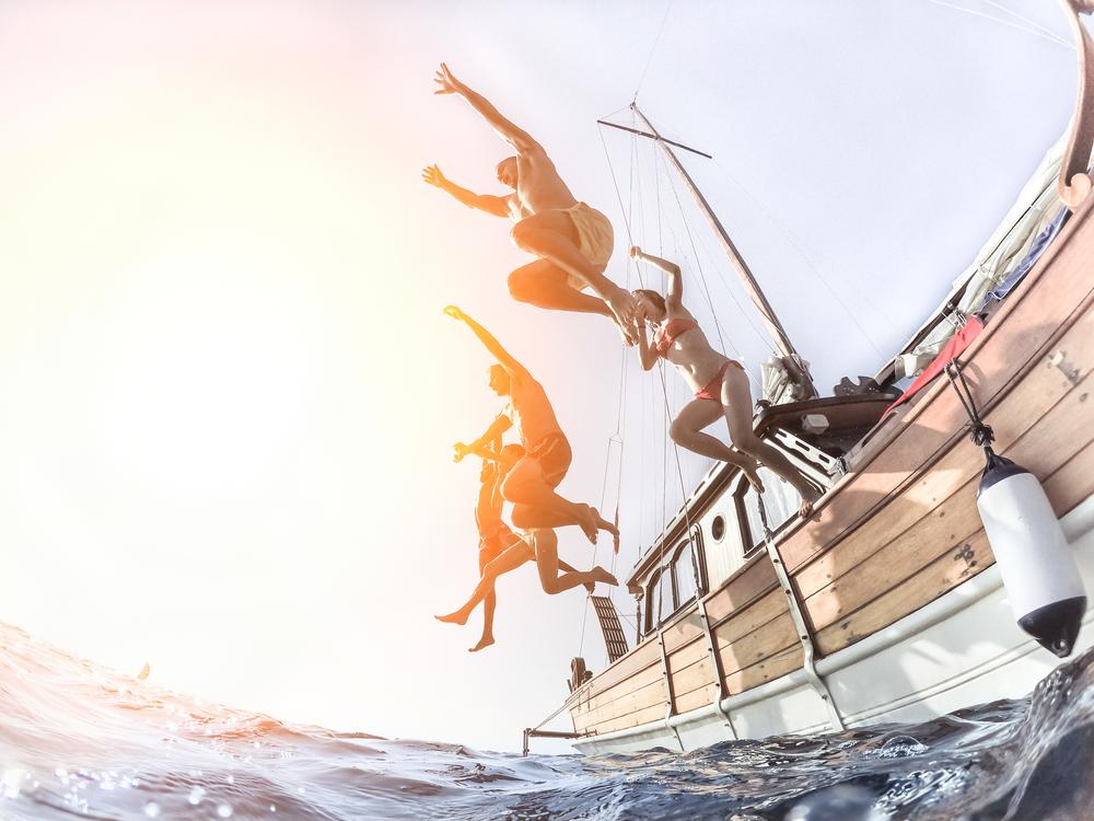junge fröhliche Leute springen vom Segelboot ins Meer am einem Sommertag - Urlaubs- und Freundschaftskonzept