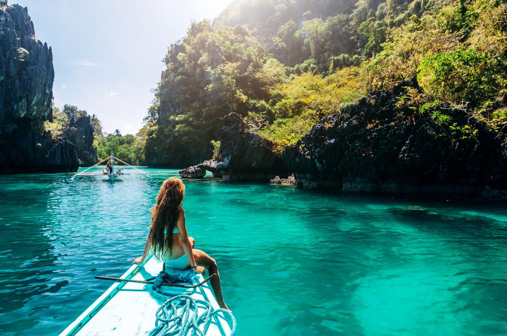 Junge Frau entspannen auf einem Boot und blickt auf die Insel. Reise nach Asien: El Nido, Palawan, Philippinen.