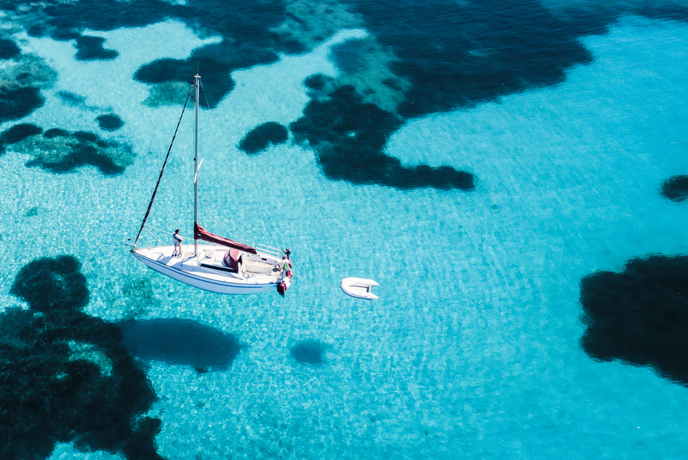 Luftbild eines Segelbootes vor der Insel Mortorio auf Sardinien. Der Strand mit türkisfarbenem und transparentem Meer. Emerald Coast, Sardinien, Italien.