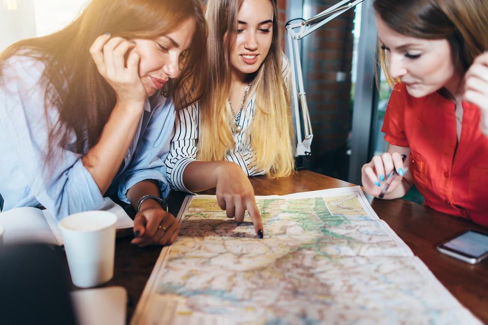 Drei Freundinnen planen ihren Urlaub am Tisch, und sitzen vor einer  Karte um das Ziel auszuwählen