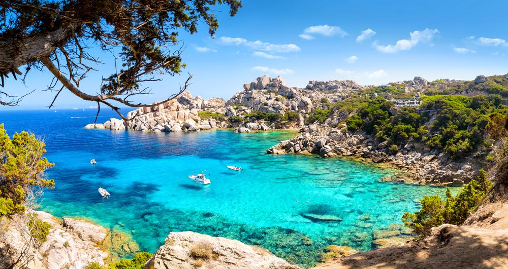 Bucht der italienische Insel Sardinien im Mittelmeer mit türkisfarbenen Wasser und Booten