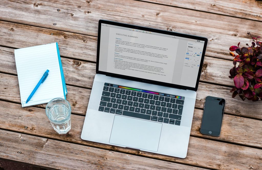 Laptop steht auf einem Holztisch, daneben liegt ein Smartphone, ein Block mit Stift und ein Glas Wasser