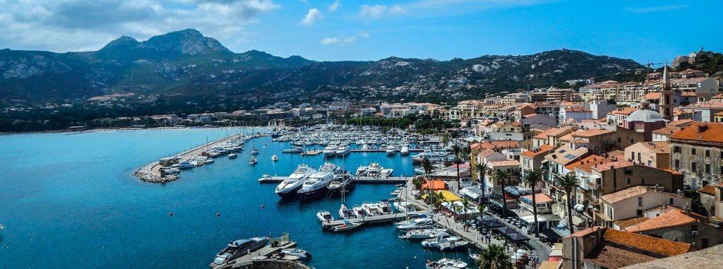 Blick auf den Hafen von Calvi mit vielen Booten un der Stadt im Hintergrund, Korsika
