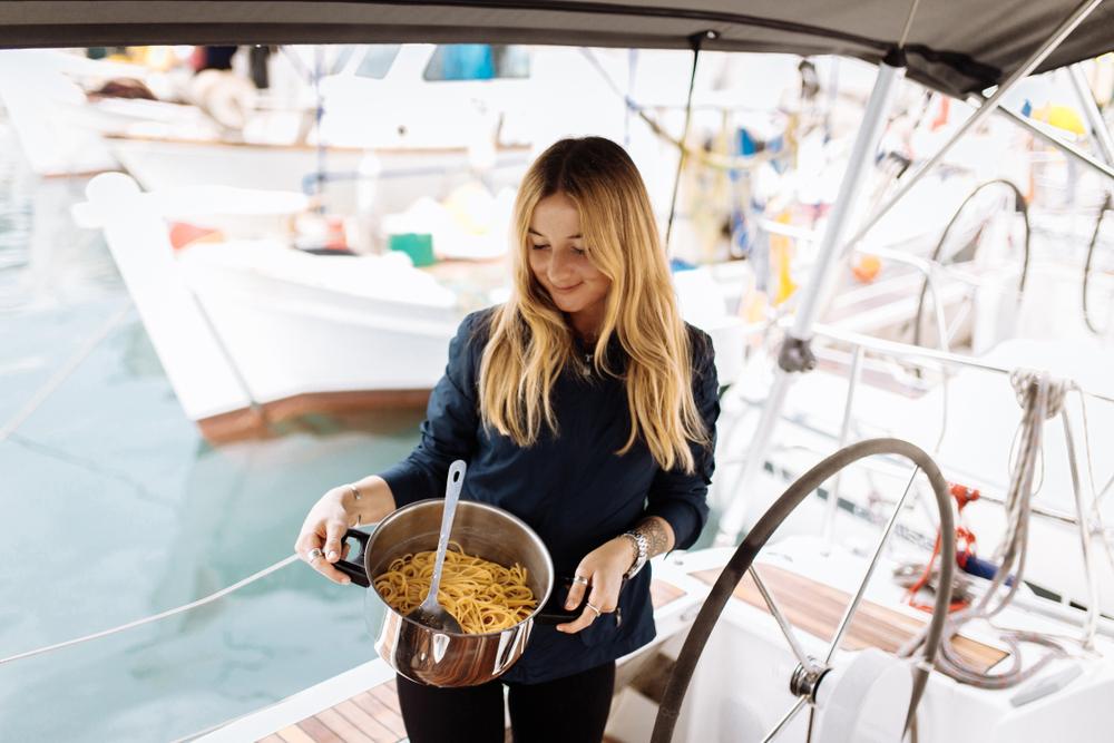 Frau hält einen Topf mit Pasta in der Hand und steht auf einem Segelboot