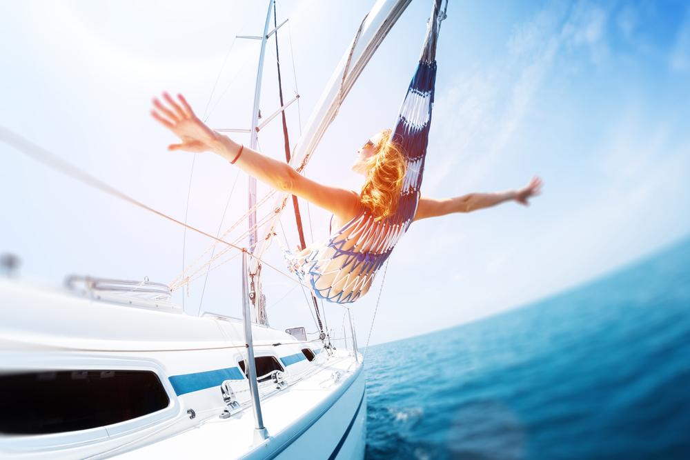 Junge Frau genießt tropisches Segeln in der Hängematte auf der Yacht. Kippverschiebungseffekt angewendet
