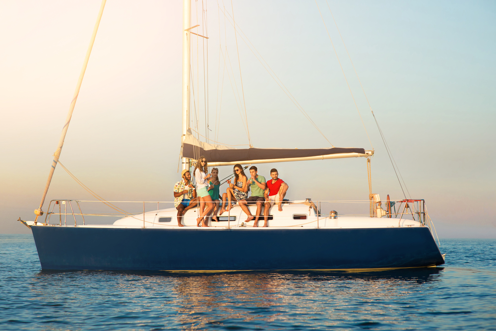 Jungs und Mädchen auf Yacht. Menschen mit Getränken auf dem Schiff. Gesellschaft der Freunde.