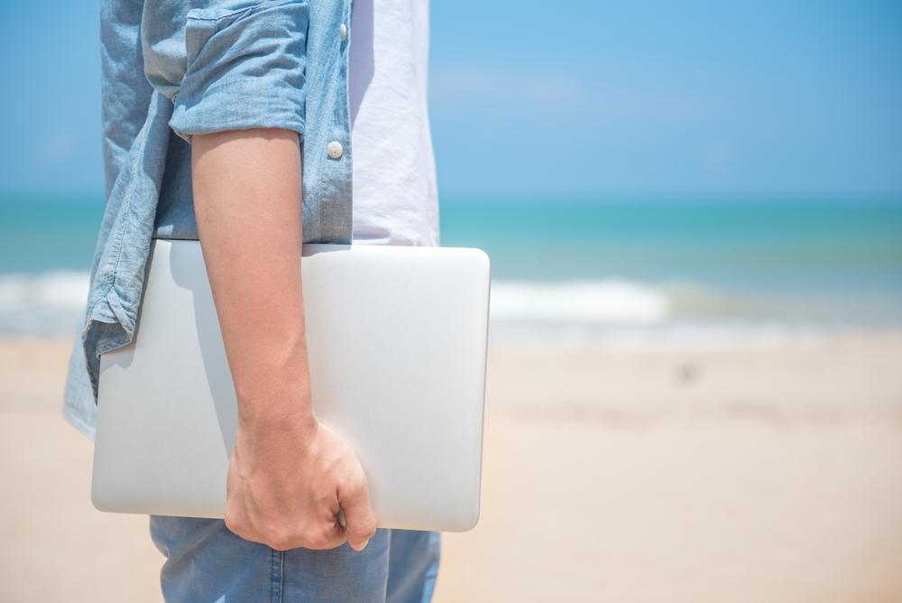 Mann, der am Strand einen Laptop hält, im Sommer draußen arbeitet, digitale Nomad-Lifestyle-Konzepte