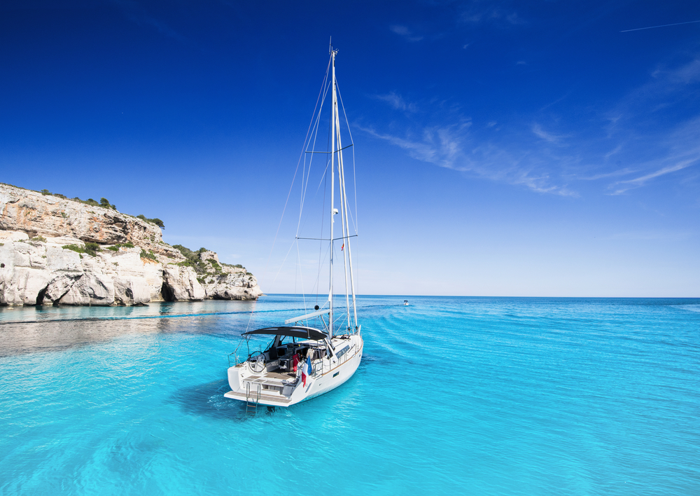 Schöne Bucht mit einer Segelbooten Yacht, Menorca Insel, Spanien. Reise und aktives Lifestyle-Konzept