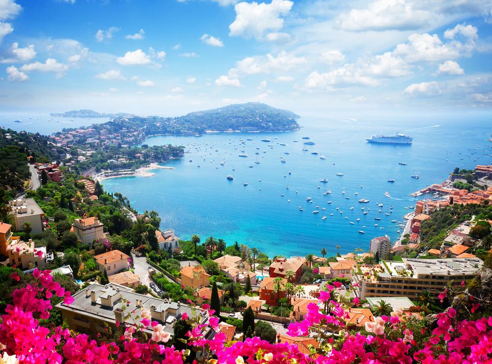 Landschaft an der Riviera Küste, türkises Wasser, Blumen und blauer Himmel der Cote d'Azur im Sommer, Frankreich