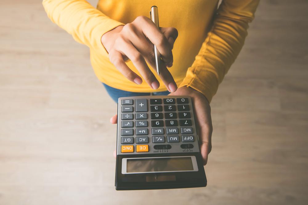 Unternehmerin, die einen Taschenrechner mit Stift in der Hand verwendet und dabei die finanziellen Kosten berechnet