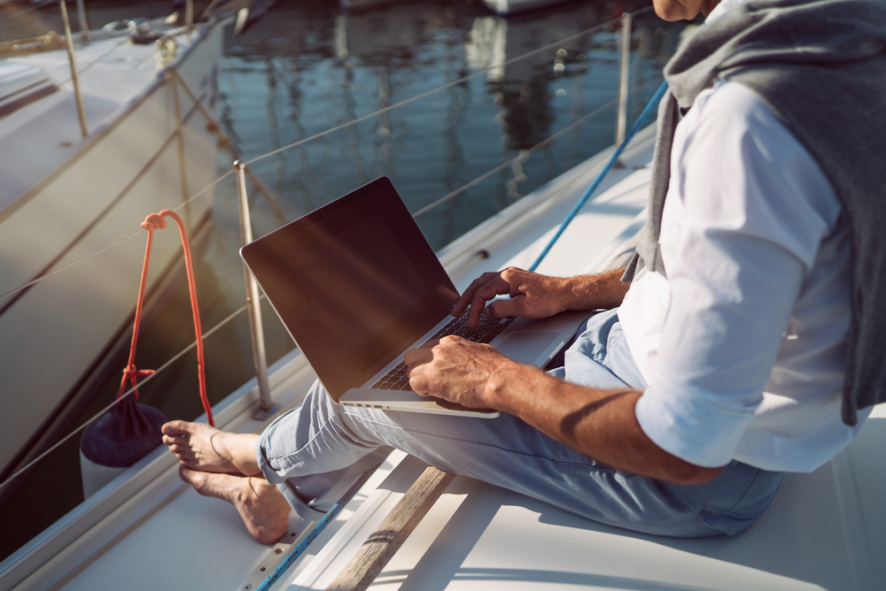 Mann sitzt mit seinem Laptop auf einem Boot und arbeitet