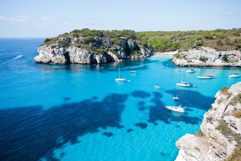 Blick auf die Cala Macarella auf Menora mit Booten im türkisfarbenen Wasser vor der Bucht