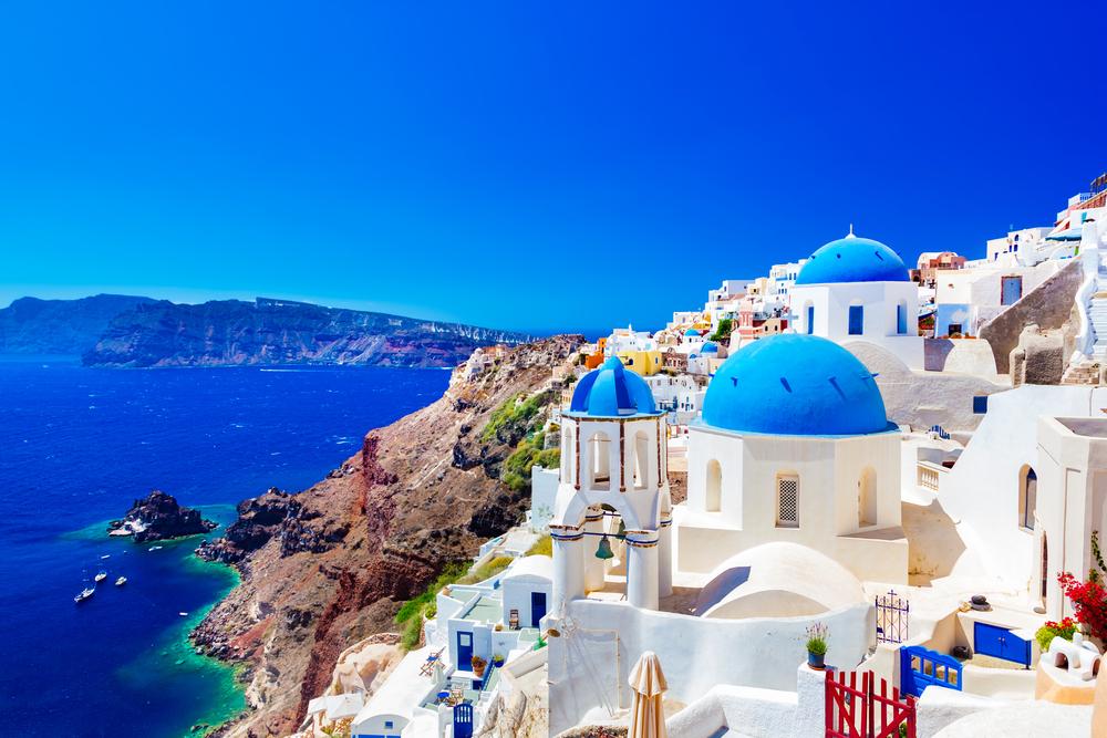Oia Stadt auf Santorini Insel, Griechenland. Traditionelle und berühmte Häuser und Kirchen mit blauen Kuppeln über der Caldera, dem Ägäischen Meer