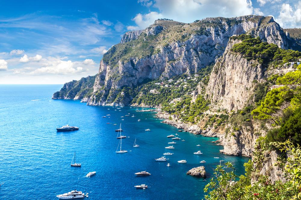 Capri Insel mit vielen Booten auf dem Wasser an einem schönen Sommertag in Italien